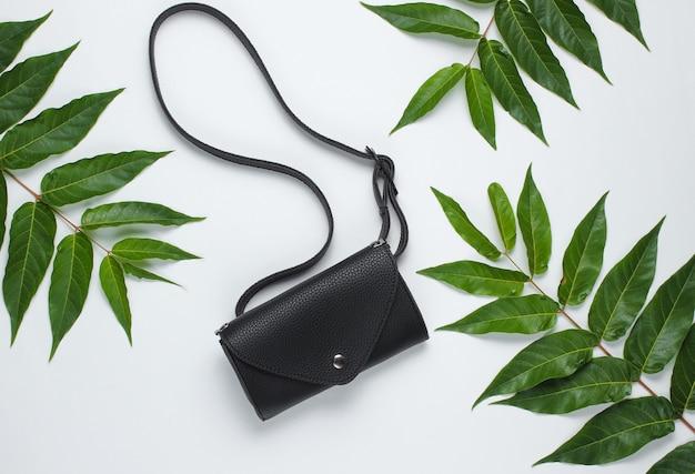 Bolsa de cintura de couro em fundo branco com folhas verdes tropicais. vista do topo