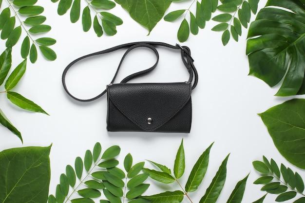 Bolsa de cintura de couro em fundo branco com folhas verdes tropicais.