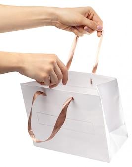 Bolsa de compras. feminino mão segurando o saco de compras em branco