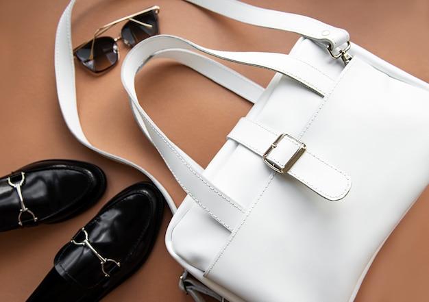 Bolsa de couro branco e sapatos preguiçosos.