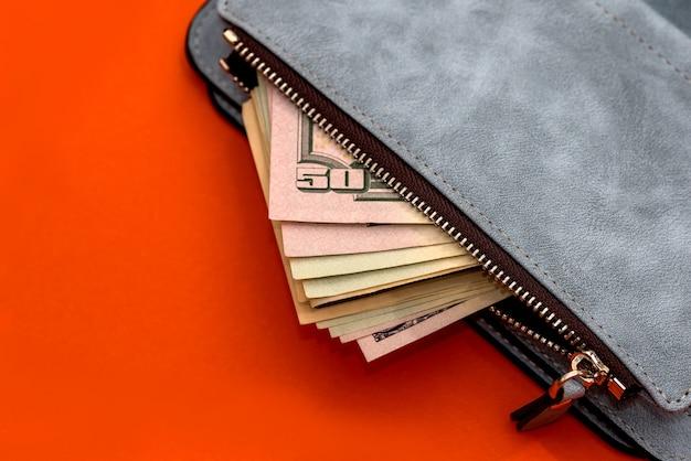 Bolsa de couro com notas de dólares