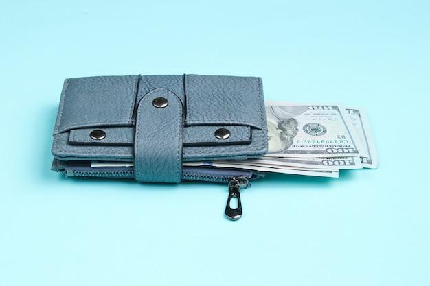 Bolsa de couro e notas de cem dólares em azul.