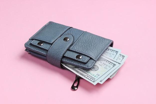 Bolsa de couro e notas de cem dólares em rosa.