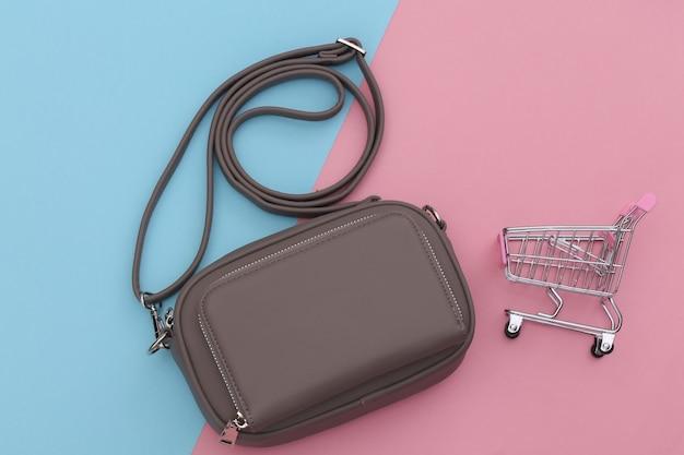 Bolsa de couro elegante com carrinho de compras em fundo rosa pastel azul. conceito de compras. vista do topo.