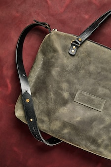 Bolsa de couro feita de couro cinza, feita à mão em um pedaço de couro cor de vinho, close-up.