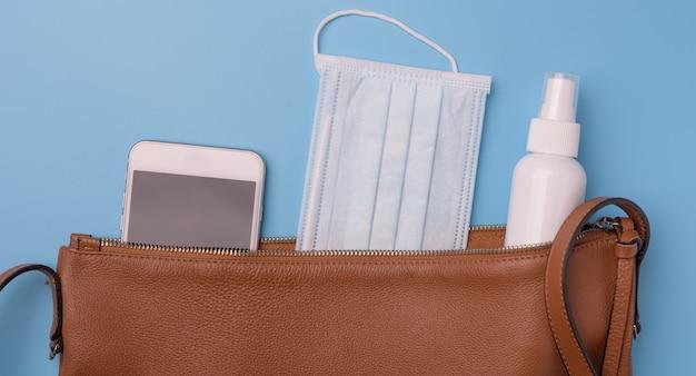 Bolsa de couro feminina com máscaras, gel de mão e telefone celular, vista superior