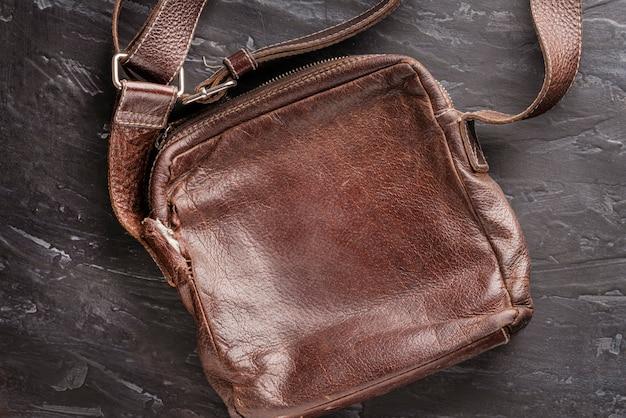 Bolsa de couro marrom elegante com uma alça de ombro em uma estrutura escura com textura. volta bom conceito e plano de fundo para o layout