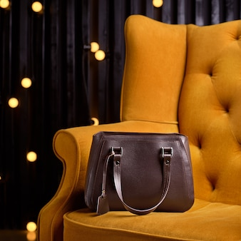 Bolsa de couro marrom para mulher de negócios na poltrona amarela.