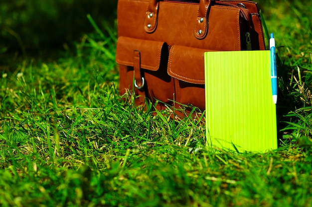 Bolsa de couro marrom retrô e notebook na grama de verão colorido brilhante no parque
