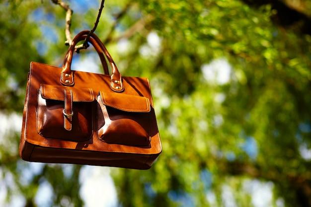 Bolsa de couro marrom retrô no parque de verão colorido brilhante pendurado nas folhas