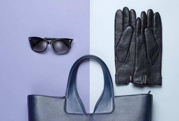 Bolsa de couro, óculos escuros, luvas em fundo cinza-roxo. vista do topo