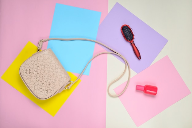 Bolsa de couro, pente, frasco de perfume em uma superfície colorida pastel. minimalismo. vista do topo