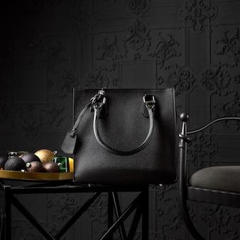 Bolsa de couro preta moderna para uma mulher de negócios em uma mesa de café.