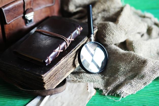 Bolsa de couro velha com uma lupa sobre um fundo de mesa de madeira marrom de viajante com espaço de cópia.