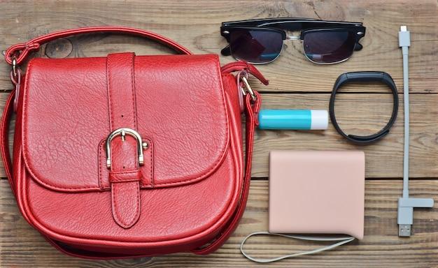 Bolsa de couro vermelha e outro layout de acessórios femininos em uma mesa de madeira. vista do topo. tendência do minimalismo. postura plana.