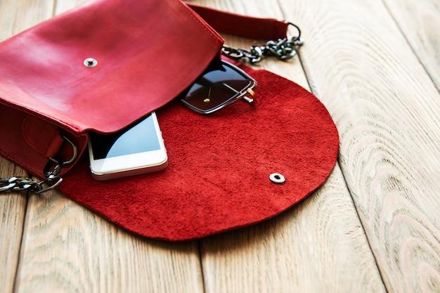 Bolsa de couro vermelha e telefone