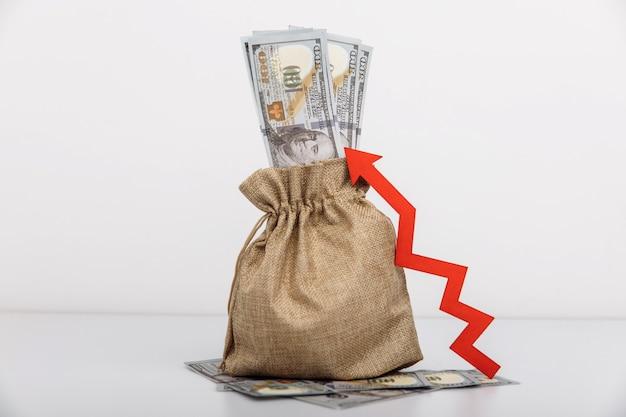 Bolsa de dinheiro e seta vermelha para cima influxo de investimento e aumento de capital de riqueza