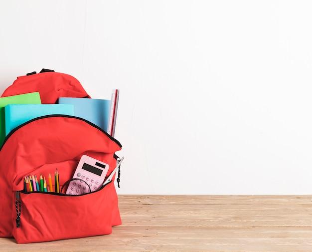 Bolsa de escola vermelha com suprimentos essenciais
