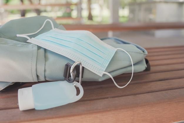Bolsa de estudante com máscara médica e clipe de desinfetante para as mãos, reabertura da escola