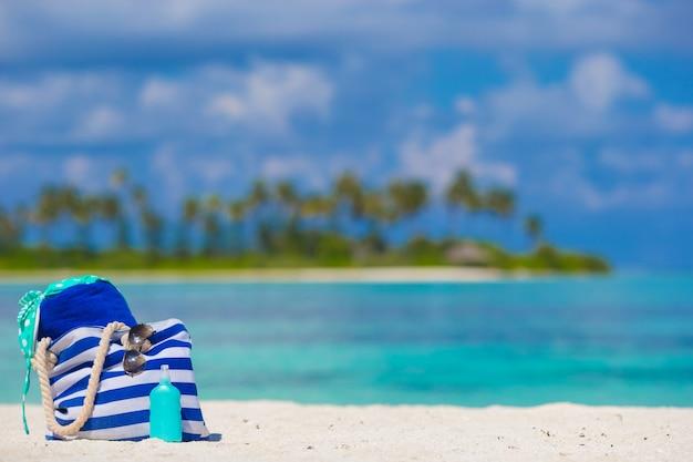 Bolsa de listra, toalha azul, óculos de sol, protetor solar, garrafa e maiô fundo água turquesa e palmeiras verdes