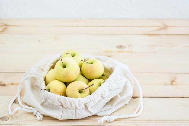 Bolsa de lona com laços com maçãs em um fundo de madeira natural