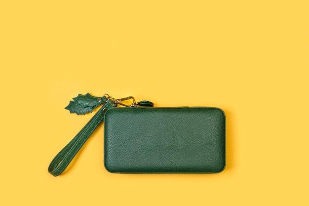 Bolsa de mão verde sobre fundo amarelo