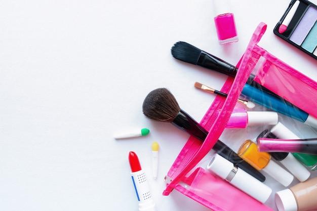 Bolsa de maquiagem com cosméticos e acessórios em um fundo branco