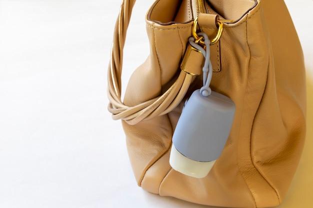 Bolsa de mulher com tubo de álcool gel para higiene das mãos. espaço para texto