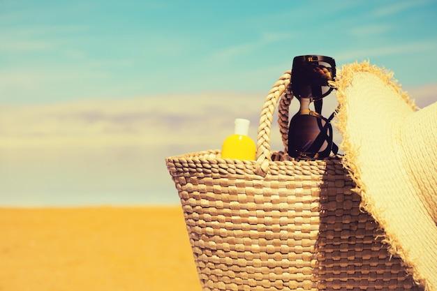 Bolsa de palha, óculos escuros, uma garrafa de protetor solar e um chapéu com a praia do mar morto.