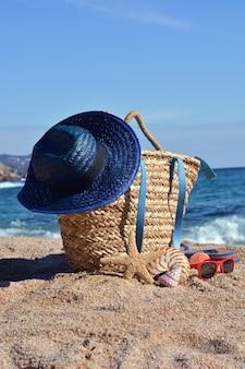 Bolsa de praia com um livro e um telefone e óculos de sol, acompanhados por uma estrela do mar