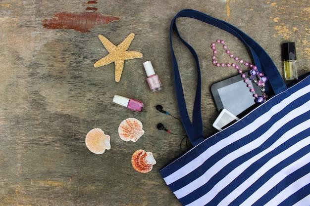 Bolsa de praia, cosméticos e acessórios femininos em madeira velha