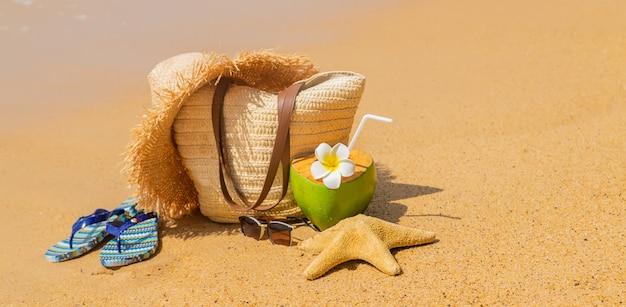 Bolsa de praia e coco no mar.