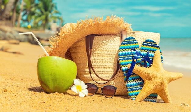 Bolsa de praia e coco no mar