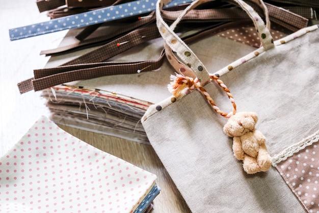 Bolsa de tecido pendurada boneca de urso em fundo de madeira