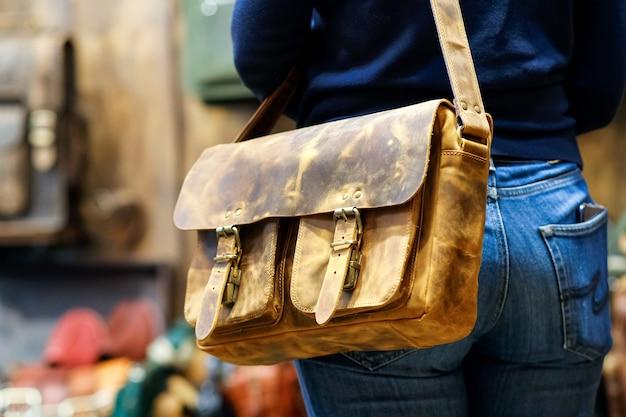 Bolsa de viagem de ombro no ombro de uma jovem em jeans apertados sexy no contexto de outras bolsas da loja. o conceito de produtos de couro natural.