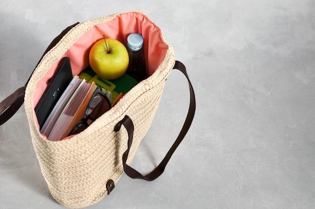 Bolsa de vime na moda elegante com livros didáticos e cadernos