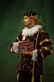Bolsa do empresário. retrato de jovem medieval em roupas vintage, em pé sobre fundo escuro. modelo masculino como duque, príncipe, pessoa real. conceito de comparação de eras, moderno, moda.