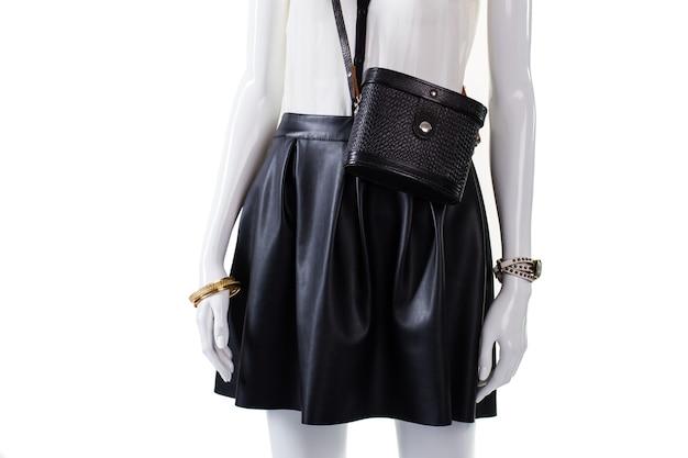 Bolsa e saia em manequim. bolsa retrô com saia de couro. saia escura da moda feminina. pulseira de ouro e bolsa preta.