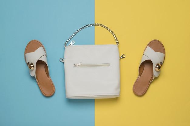 Bolsa e sandálias de mulher branca em um fundo amarelo e azul. acessórios de moda feminina. postura plana.