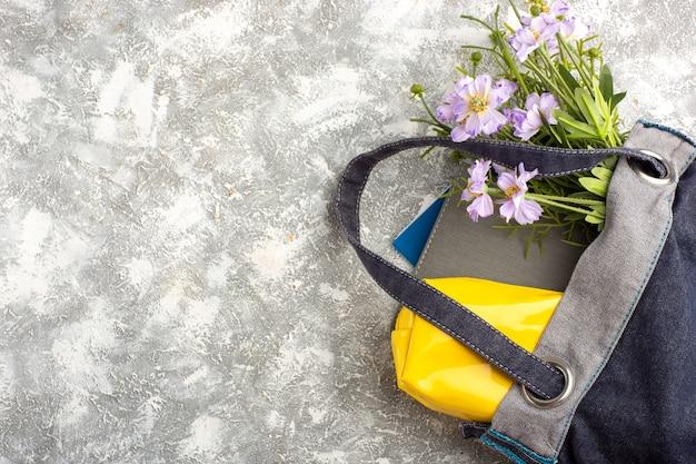 Bolsa escura de vista superior com cadernos e flores na superfície branca