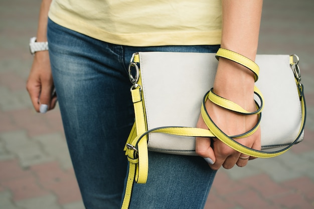 Bolsa feminina cinza-amarela nas mãos femininas close-up