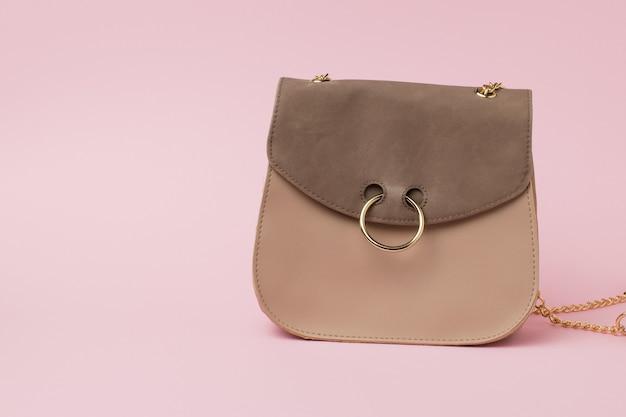 Bolsa feminina de camurça com um anel de ouro na fechadura em uma superfície rosa