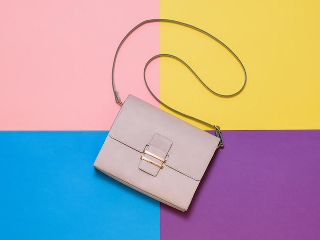 Bolsa feminina de couro claro sobre um fundo de quatro cores. acessório de moda feminina. estilo simples. a vista do topo.