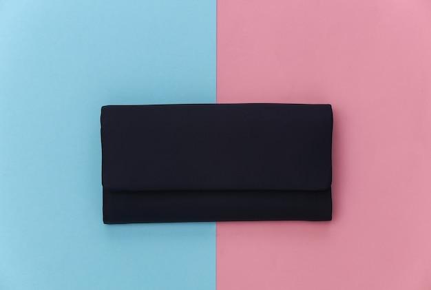 Bolsa feminina de couro preto sobre fundo azul-rosa pastel. vista do topo