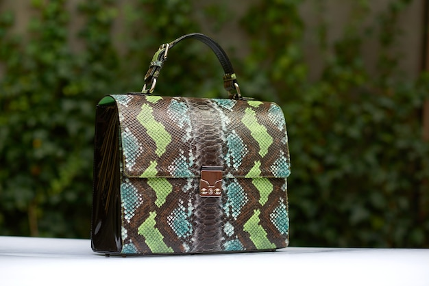 Bolsa feminina estilosa com imitação de pele de cobra, confeccionada nas cores azul, verde e marrom. tem alças pequenas.