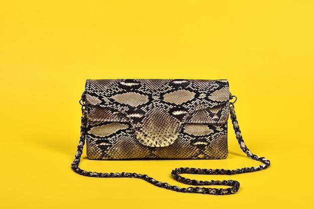 Bolsa feminina pequena feita de pele de cobra genuína em uma superfície amarela brilhante