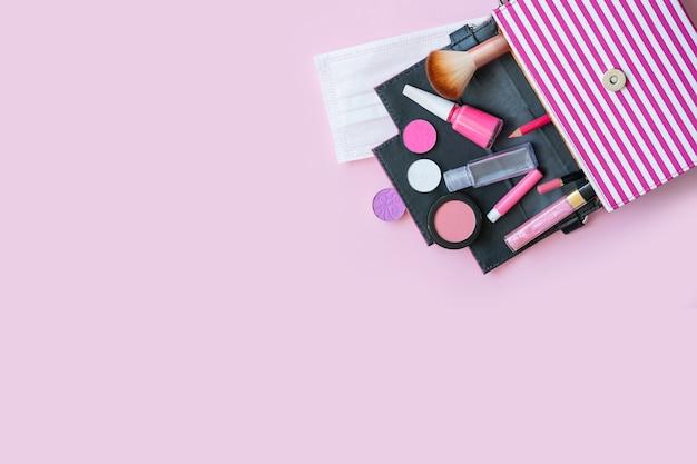 Bolsa feminina rosa com cosméticos para maquiagem, sombra para os olhos, brilho labial, esmalte, blush, escova, máscara e desinfetante, cosméticos rosa em um fundo rosa