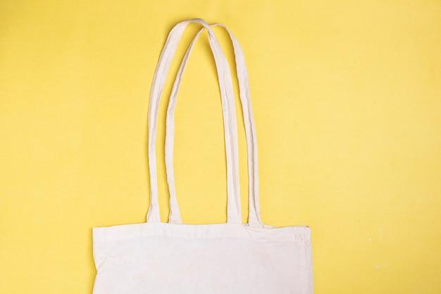 Bolsa maquete lona de algodão. saco de têxteis ecológicos em papel amarelo, vista superior