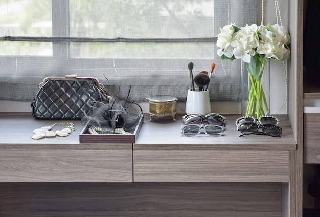 Bolsa, óculos escuros, jóias e pincéis de maquiagem em uma penteadeira de madeira