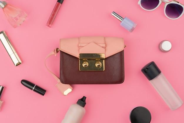 Bolsa pequena feminina cheia de produtos cosméticos em fundo rosa brilhante